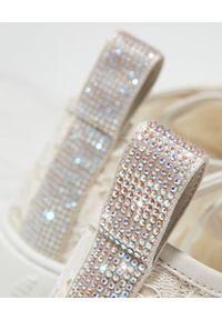 RENE CAOVILLA - Kremowe sneakersy Lace z kryształami. Kolor: beżowy. Materiał: tkanina, koronka, guma. Wzór: aplikacja, napisy