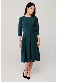 Marie Zélie - Sukienka Chione butelkowa zieleń. Typ kołnierza: dekolt w łódkę. Materiał: bawełna, materiał, elastan, tkanina, poliamid. Sezon: lato, zima. Styl: wizytowy