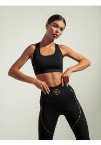 4f - Biustonosz treningowy ze średnim wsparciem damski Anna Lewandowska x 4F. Kolor: czarny. Materiał: satyna. Wzór: nadruk. Sport: kolarstwo, fitness