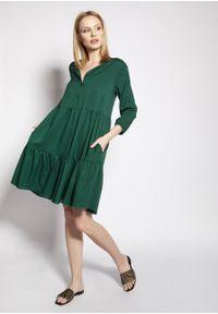 e-margeritka - Sukienka trapezowa koszulowa z falbanami zielona - 38/40. Kolekcja: moda ciążowa. Kolor: zielony. Materiał: tkanina, wiskoza, materiał. Sezon: lato. Typ sukienki: koszulowe, trapezowe