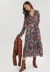 Born2be - Czarna Sukienka Qinrahne. Typ kołnierza: kokarda. Kolor: czarny. Materiał: materiał. Wzór: kwiaty, aplikacja. Typ sukienki: kopertowe, rozkloszowane. Długość: maxi