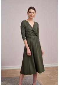 Marie Zélie - Sukienka Rita oliwkowa – mikromodal. Typ kołnierza: dekolt kopertowy. Kolor: oliwkowy. Materiał: wiskoza, dzianina, elastan, włókno, skóra. Długość rękawa: krótki rękaw. Typ sukienki: proste, kopertowe