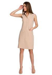 Style - Żakietowa sukienka ze stójką elegancka beżowa. Typ kołnierza: kołnierzyk stójkowy. Kolor: beżowy. Materiał: elastan. Długość rękawa: bez rękawów. Styl: elegancki