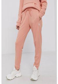adidas Originals - Spodnie. Kolor: pomarańczowy. Materiał: bawełna, dzianina. Wzór: gładki