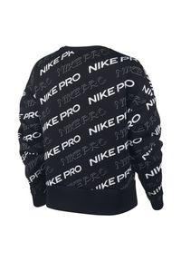 Bluza damska Nike Pro CJ3588. Materiał: materiał. Technologia: Dri-Fit (Nike). Wzór: nadruk. Sport: fitness