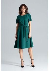 e-margeritka - Sukienka rozkloszowana elegancka zielona - m. Okazja: do pracy. Typ kołnierza: dekolt w łódkę. Kolor: zielony. Materiał: wiskoza, poliester, materiał. Długość rękawa: krótki rękaw. Typ sukienki: rozkloszowane. Styl: elegancki