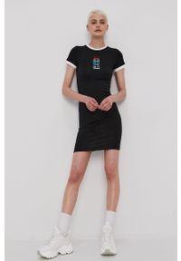 Ellesse - Sukienka. Kolor: czarny. Materiał: dzianina. Długość rękawa: krótki rękaw. Wzór: aplikacja. Typ sukienki: dopasowane