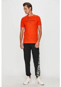 Pomarańczowy t-shirt Calvin Klein Jeans na co dzień, casualowy, z okrągłym kołnierzem, z nadrukiem