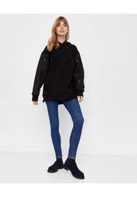 MONCLER - Czarna bluza z logo na plecach. Okazja: na co dzień. Kolor: czarny. Materiał: dresówka, nylon, bawełna, jeans. Długość rękawa: długi rękaw. Długość: długie. Wzór: aplikacja. Sezon: jesień. Styl: klasyczny, casual