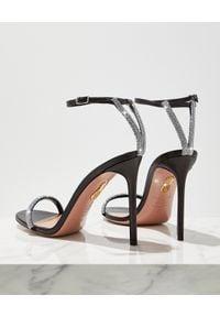 AQUAZZURA - Czarne sandały na szpilce Moon Crystal. Okazja: na co dzień. Nosek buta: okrągły. Zapięcie: pasek. Kolor: czarny. Wzór: aplikacja, paski. Obcas: na szpilce. Styl: klasyczny, wizytowy, casual. Wysokość obcasa: średni
