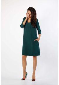 Nommo - Zielona Trapezowa Sukienka w Serek z Kieszeniami. Typ kołnierza: dekolt w serek. Kolor: zielony. Materiał: wiskoza, poliester. Typ sukienki: trapezowe