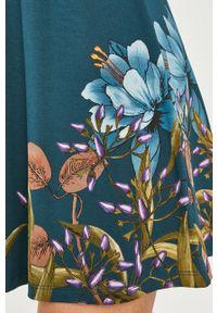 Desigual - Sukienka. Kolor: turkusowy. Materiał: dzianina. Długość rękawa: krótki rękaw. Wzór: nadruk. Typ sukienki: rozkloszowane