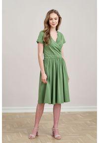 Marie Zélie - Sukienka Larissa zieleń wiosenna krótki rękaw XL zielony. Typ kołnierza: dekolt kopertowy. Kolor: zielony. Materiał: materiał, bawełna, dzianina, skóra, elastan. Długość rękawa: krótki rękaw. Sezon: wiosna. Typ sukienki: kopertowe