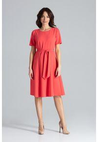 Lenitif - Trapezowa sukienka o klasycznym kroju z paskiem koralowa. Okazja: do pracy. Kolor: pomarańczowy. Wzór: gładki. Typ sukienki: trapezowe. Styl: klasyczny. Długość: midi