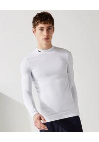 Lacoste - LACOSTE - Biały longsleeve z tkaniny technicznej. Kolor: biały. Materiał: tkanina. Długość rękawa: długi rękaw. Długość: długie. Wzór: haft, aplikacja. Styl: sportowy