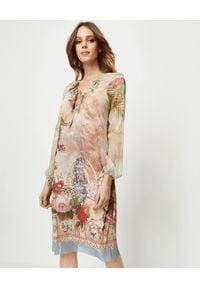ANA ALCAZAR - Beżowa sukienka z nadrukiem. Typ kołnierza: kołnierz z falbankami. Kolor: beżowy. Materiał: materiał. Długość rękawa: długi rękaw. Wzór: nadruk. Długość: mini