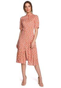 Style - Sukienka midi w duże grochy z asymetryczną falbaną łososiowa. Kolor: różowy. Wzór: grochy. Typ sukienki: asymetryczne. Styl: retro. Długość: midi