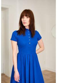 Marie Zélie - Sukienka Polo niebieska – marszczona. Okazja: do pracy, na co dzień. Typ kołnierza: polo. Kolor: niebieski. Materiał: bawełna, dzianina, materiał. Długość rękawa: krótki rękaw. Typ sukienki: proste, sportowe. Styl: wakacyjny, sportowy, klasyczny, casual