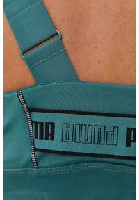 Puma - Biustonosz sportowy. Kolor: zielony. Rodzaj stanika: odpinane ramiączka, wyciągane miseczki