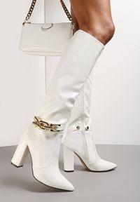 Renee - Białe Kozaki Nikolio. Nosek buta: szpiczasty. Zapięcie: zamek. Kolor: biały. Szerokość cholewki: normalna. Wzór: gładki, aplikacja. Wysokość cholewki: przed kolano. Obcas: na obcasie. Styl: elegancki. Wysokość obcasa: wysoki
