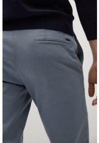 Mango Man - Spodnie BARNA. Kolor: niebieski. Materiał: tkanina, bawełna. Wzór: gładki