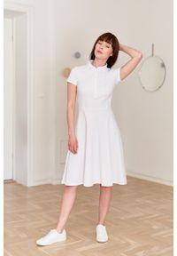 Marie Zélie - Sukienka Polo biała – trapezowa. Okazja: do pracy, na co dzień. Typ kołnierza: polo. Kolor: biały. Materiał: bawełna, dzianina, materiał. Długość rękawa: krótki rękaw. Typ sukienki: trapezowe. Styl: wakacyjny, sportowy, klasyczny, casual
