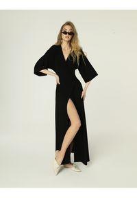 Madnezz - Sukienka Monica - czarna. Okazja: na spotkanie biznesowe. Kolor: czarny. Materiał: wiskoza, elastan. Typ sukienki: proste, kopertowe. Styl: wakacyjny, biznesowy. Długość: midi