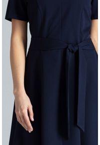 Lenitif - Trapezowa sukienka o klasycznym kroju z paskiem granatowa. Okazja: do pracy. Kolor: niebieski. Wzór: gładki. Typ sukienki: trapezowe. Styl: klasyczny. Długość: midi