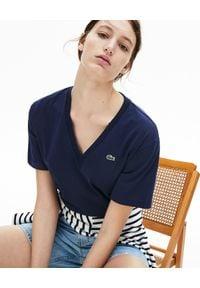 Lacoste - LACOSTE - Granatowy t-shirt z haftem w serek. Typ kołnierza: dekolt w serek. Kolor: niebieski. Materiał: jeans, prążkowany, bawełna. Wzór: haft