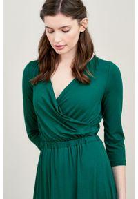 Marie Zélie - Sukienka Rita ciemnozielona. Typ kołnierza: dekolt kopertowy. Kolor: zielony. Materiał: wiskoza, dzianina, materiał, elastan. Długość rękawa: krótki rękaw. Typ sukienki: proste, kopertowe