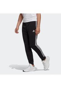 Adidas - Spodnie dresowe fitness. Materiał: bawełna, wiskoza, poliester. Wzór: paski. Sport: fitness