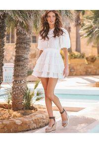 MOTIVE&MORE - Biała sukienka Cancun. Kolor: biały. Materiał: tkanina, bawełna, materiał. Wzór: haft, aplikacja, ażurowy. Sezon: lato, wiosna. Długość: mini