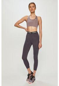 Nike - Biustonosz sportowy. Kolor: fioletowy. Materiał: włókno, skóra, tkanina. Rodzaj stanika: odpinane ramiączka. Technologia: Dri-Fit (Nike)