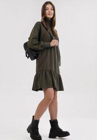 Born2be - Khaki Sukienka Dzianinowa Raipheia. Okazja: na co dzień. Typ kołnierza: golf. Kolor: brązowy. Wzór: jednolity, gładki. Typ sukienki: proste. Materiał: dzianina. Długość rękawa: długi rękaw. Styl: casual. Długość: mini