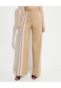 PALM ANGELS - Beżowe spodnie o luźnym kroju. Stan: podwyższony. Kolor: beżowy. Długość: długie. Wzór: aplikacja