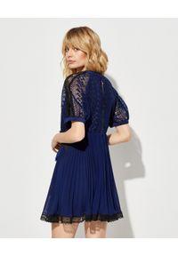 SELF PORTRAIT - Sukienka z geometryczną koronką. Kolor: czarny. Materiał: koronka. Wzór: koronka, geometria. Typ sukienki: plisowane, rozkloszowane. Długość: mini