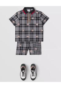 BURBERRY CHILDREN - Czarna koszulka w białą kratę 3-14 lat. Kolor: czarny. Materiał: bawełna, dzianina. Wzór: nadruk. Sezon: lato. Styl: klasyczny