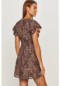 Guess - Sukienka. Kolor: brązowy. Długość rękawa: krótki rękaw. Typ sukienki: rozkloszowane