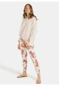 Wzorzyste bawełniane spodnie dresowe ze ściągaczami Juvia. Kolor: beżowy. Materiał: bawełna, dresówka. Wzór: nadruk