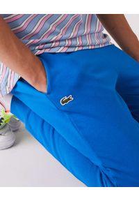 Lacoste - LACOSTE - Niebieskie spodnie dresowe Sport Tennis. Kolor: niebieski. Materiał: dresówka. Wzór: haft. Sport: fitness, kolarstwo