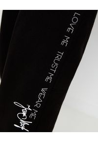 JOANNA MUZYK - Czarne spodnie dresowe Love Me. Stan: podwyższony. Kolor: czarny. Materiał: dresówka. Wzór: napisy, aplikacja