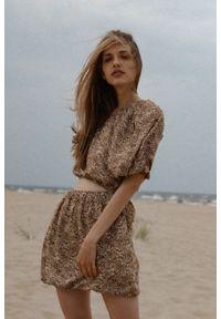 Marsala - Sukienka z wycięciem z wiskozy w kolorze beżowym w brązowe cętki - MURCIA BY MARSALA. Okazja: na imprezę. Kolor: brązowy, wielokolorowy, beżowy. Materiał: wiskoza. Typ sukienki: asymetryczne. Styl: młodzieżowy. Długość: mini