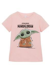 """T-shirt dziewczęcy """"The Mandalorian"""" bonprix jasnoróżowy. Kolor: różowy. Materiał: bawełna. Długość rękawa: krótki rękaw. Długość: krótkie. Wzór: napisy, nadruk"""
