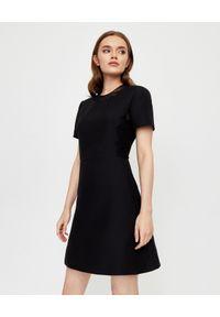 VALENTINO - Sukienka mini z koronką. Kolor: czarny. Materiał: koronka. Wzór: koronka. Typ sukienki: rozkloszowane, dopasowane, trapezowe. Styl: elegancki. Długość: mini