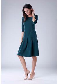 Nommo - Zielona Wizytowa Sukienka z Obniżonym Stanem. Kolor: zielony. Materiał: wiskoza, poliester. Styl: wizytowy