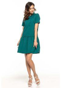 Tessita - Szmaragdowa Sukienka z Falbanką i Dekoracyjnym Wiązaniem przy Dekolcie. Kolor: zielony. Materiał: poliester, elastan