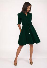 e-margeritka - Rozkloszowana delikatna sukienka koszulowa zielona - 36. Okazja: do pracy. Typ kołnierza: kołnierzyk stójkowy. Kolor: zielony. Materiał: materiał, poliester. Typ sukienki: koszulowe. Styl: wizytowy, elegancki. Długość: midi