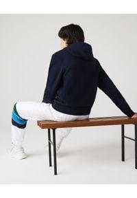 Lacoste - LACOSTE - Granatowa bluza z kapturem. Okazja: na co dzień. Typ kołnierza: kaptur. Kolor: niebieski. Materiał: jeans, bawełna, prążkowany. Wzór: aplikacja. Styl: sportowy, casual, klasyczny