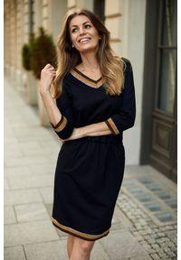 e-margeritka - Sukienka z gumką w pasie czarna - 40. Okazja: do pracy, na co dzień. Kolor: czarny. Materiał: nylon, wiskoza, materiał, elastan. Wzór: aplikacja. Typ sukienki: proste. Styl: elegancki, casual. Długość: midi