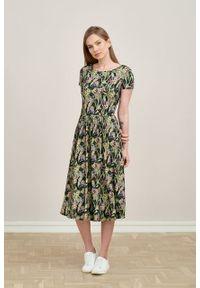 Marie Zélie - Sukienka Emelina Cynarae oliwkowa krótki rękaw. Kolor: oliwkowy. Materiał: wiskoza, dzianina, materiał, elastan, tkanina, guma. Długość rękawa: krótki rękaw. Styl: klasyczny. Długość: midi
